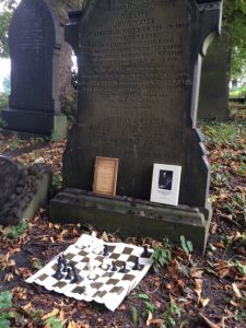 Yates' gravestone, adorned with 2 of his books and a position from his win against Vidmar San Remo 1930